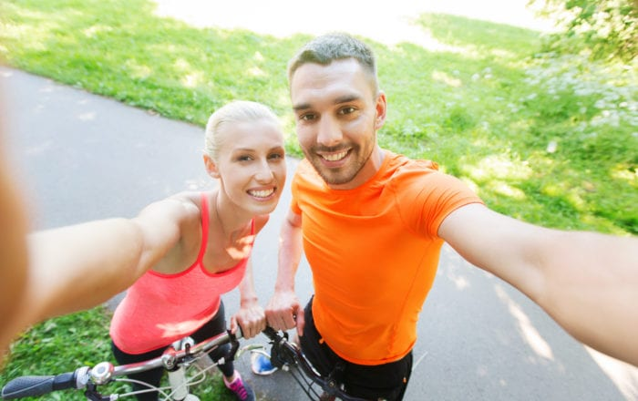 Young happy couple with bicycle taking selfie outdoors near Capewell Lofts for Ride by the River in downtown Hartford, CT