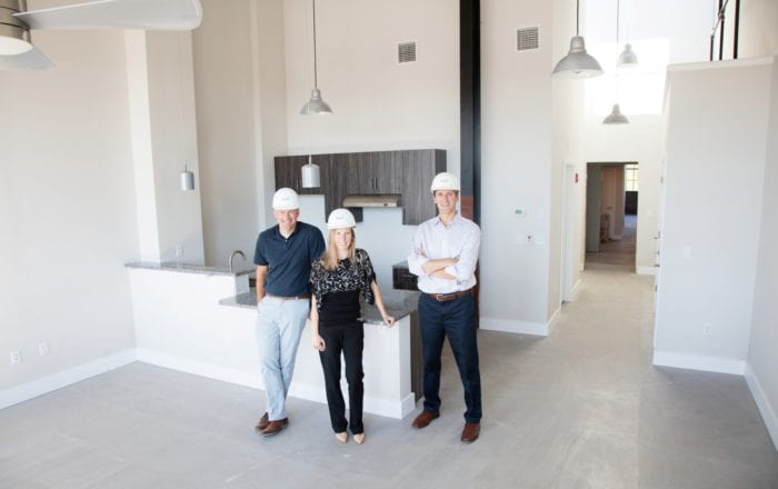 Three members of the Trio Properties team in hardhats standing in the kitchen of a newly renovated Capewell Lofts kitchen